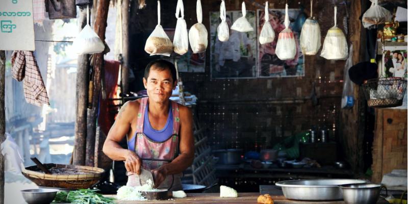 Таец стоит за прилавком небольшого уличного кафе в Тайланде